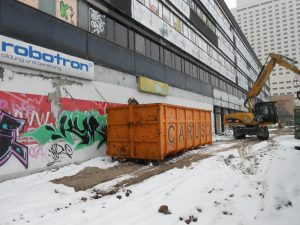 Bagger mit Ausleger vor Container